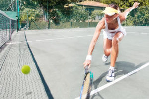 Woman on an outdoor tennis court lunging for a tennis ball with her racquet